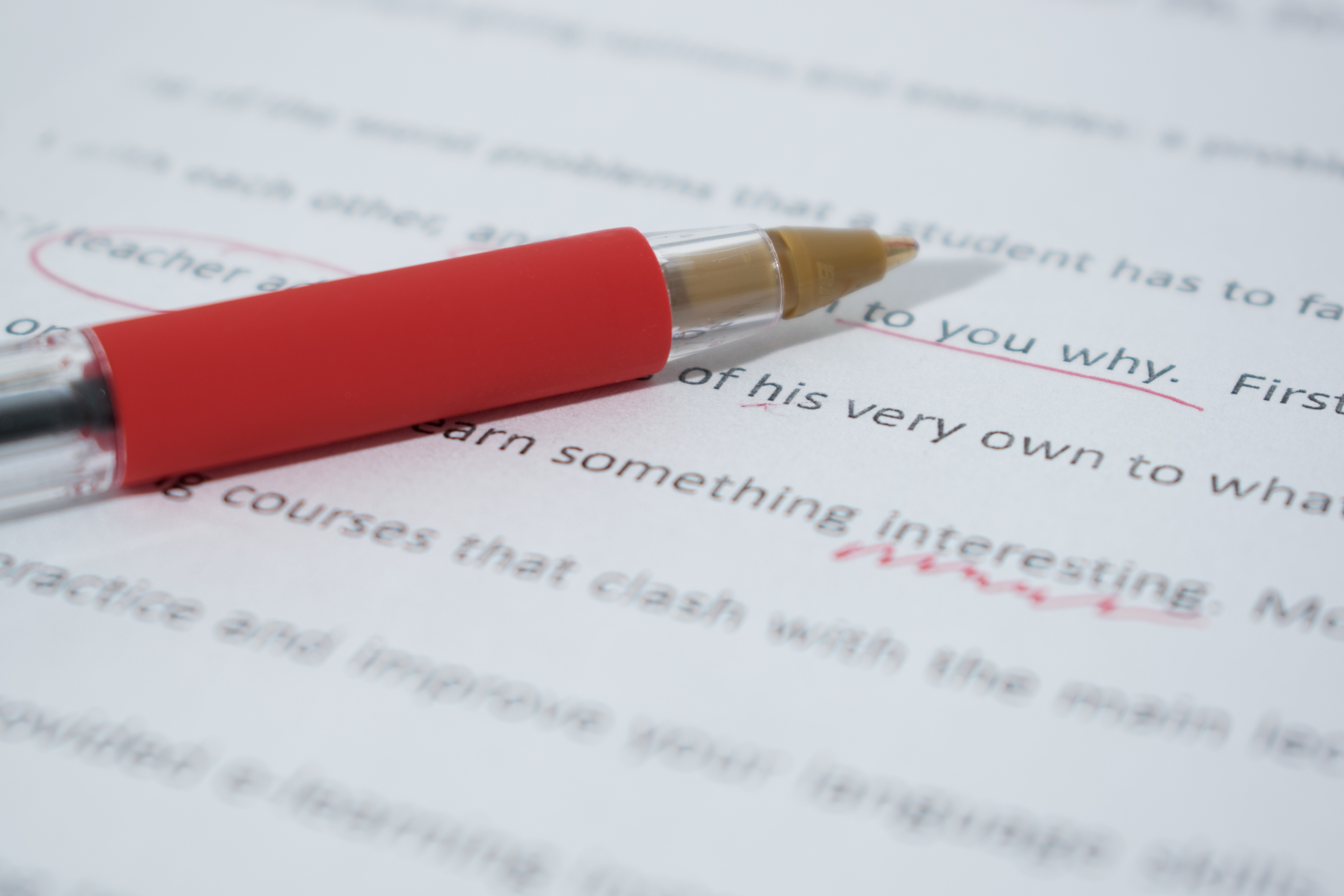 A red pen rests on top of a manuscript.