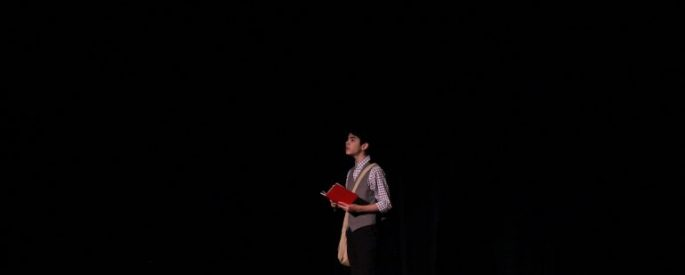 a young person on a stage is in the spotlight, reading from a red book