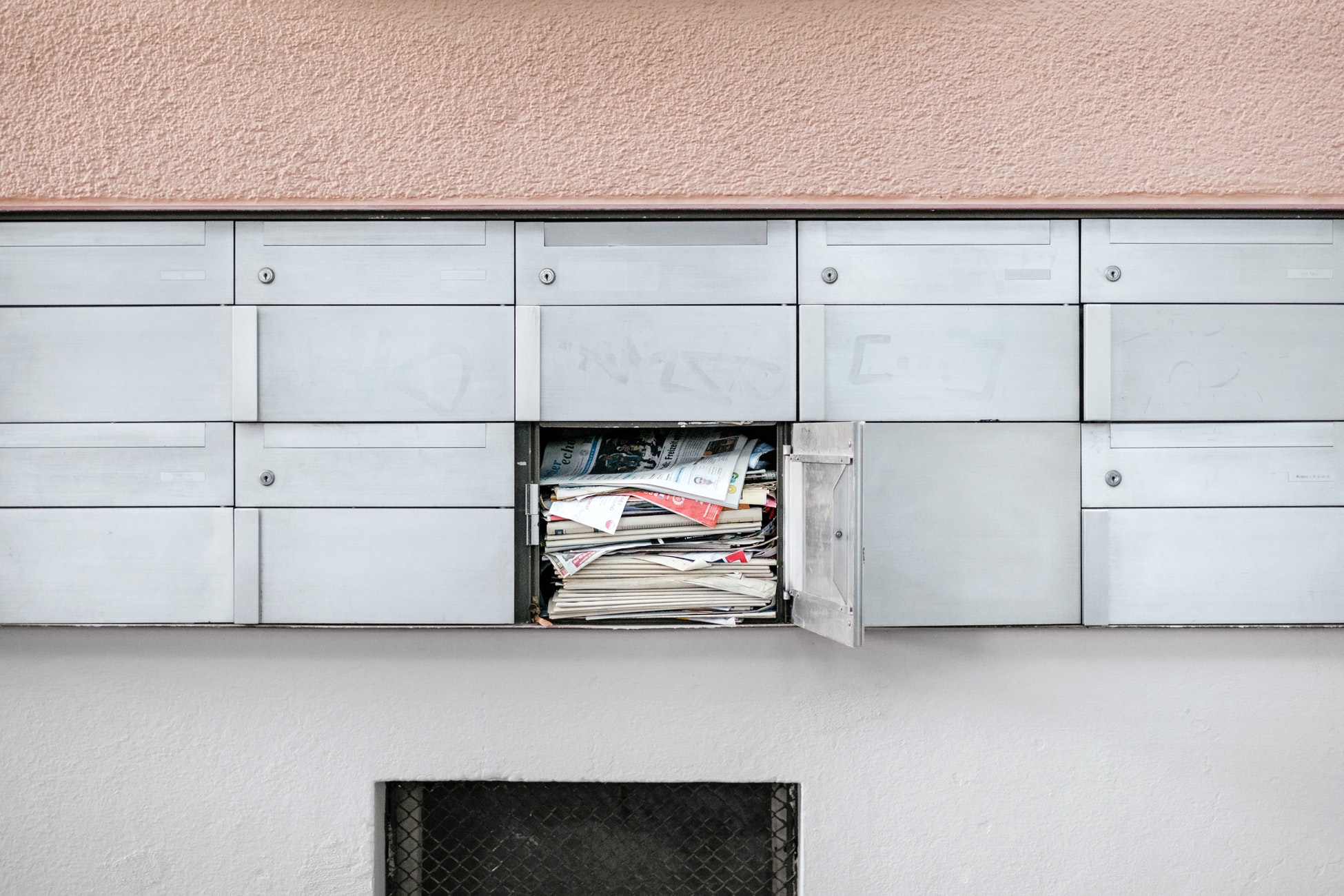 A cement wall with metal mailboxes on it with one open with mail inside of it.