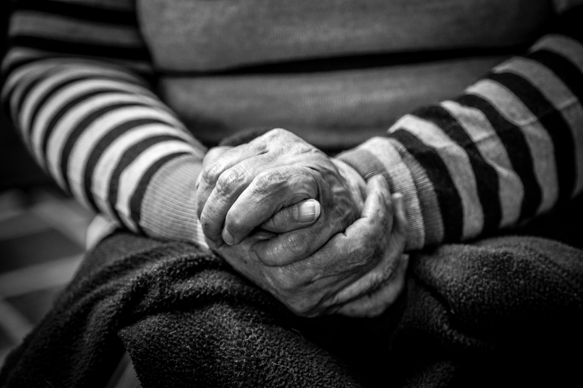 Black and white photo of a person sitting with their hands crossed on their lap.