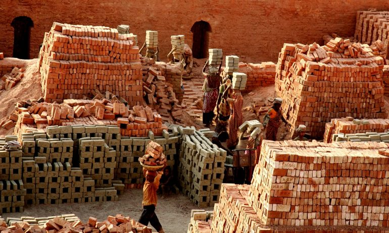 Bangladeshi women working among rows of bricks and cinderblocks - the women carry the cinderblocks and bricks above their heads