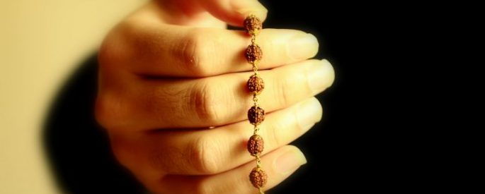 image focused on a woman's hand holding beads