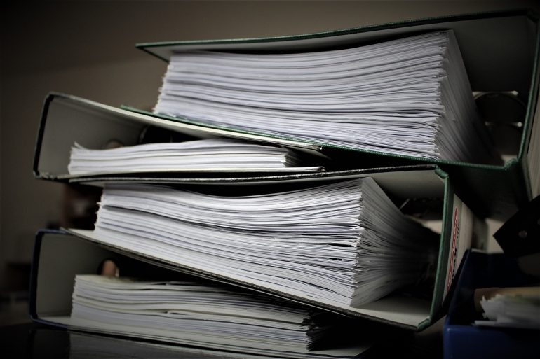 a stack of four binders full of paper in an office setting on top of each other