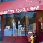 "photo of the front of a bookstore with a sign on an overhang that reads ""Downtown Books & News"""