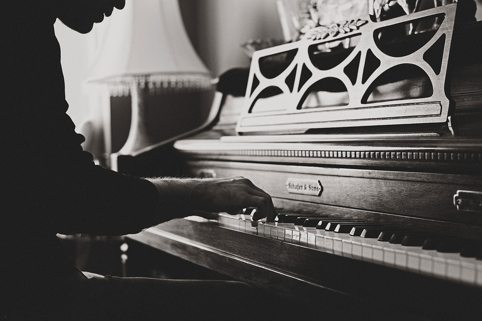 black and white photograph of a silhouetted man sitting and playing piano
