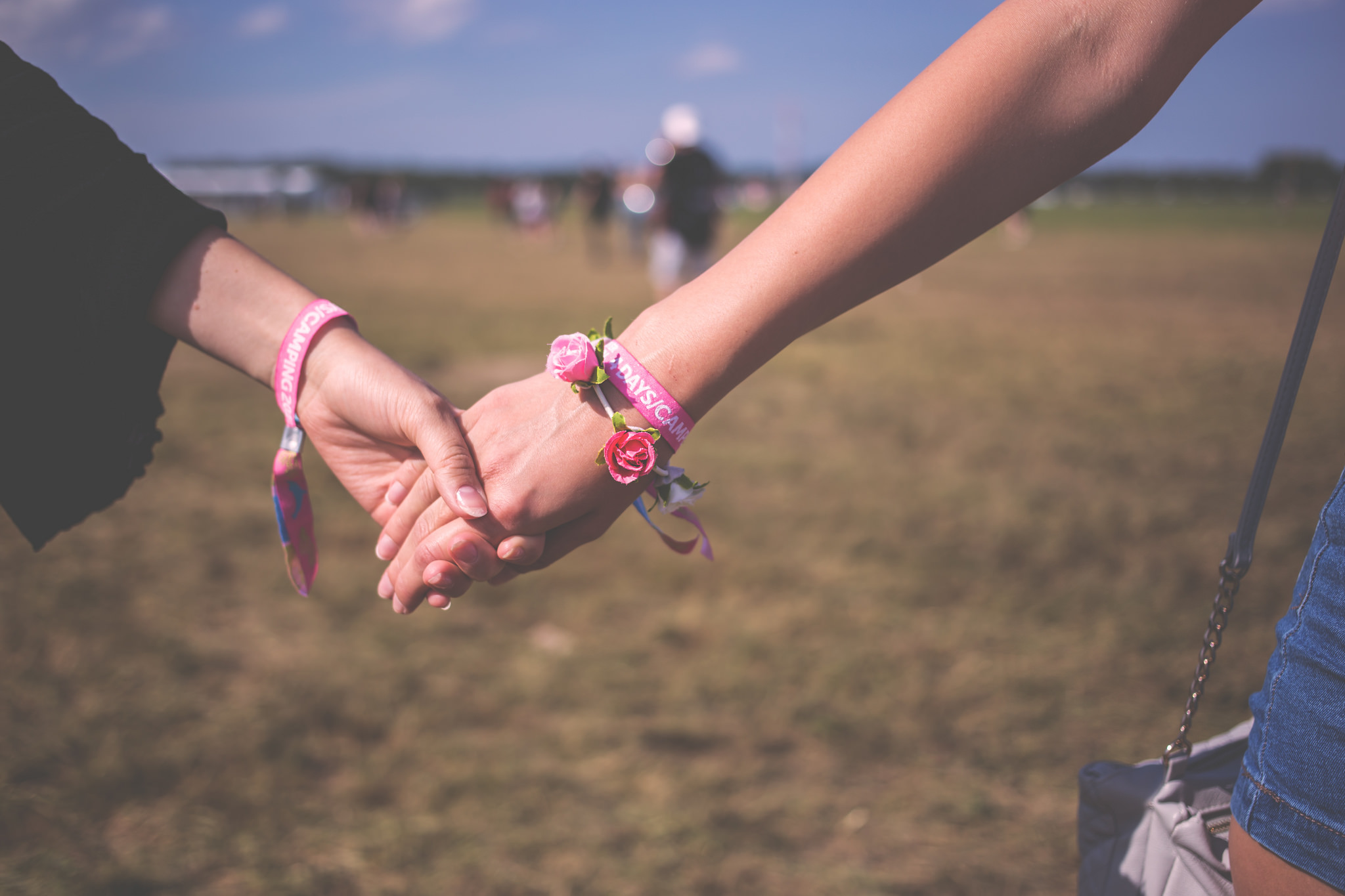 Two people holding hands wearing the same bracelets, one wears a bracelet made of small, fake roses