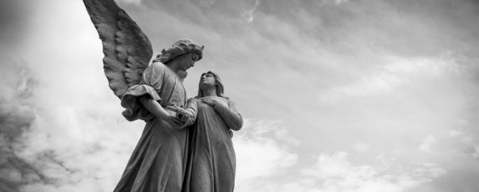black and white photograph of statues of two angels, one holds their hand over their heart, gazing into the face of the other - photo is set against a cloudy sky and the angels are off-center