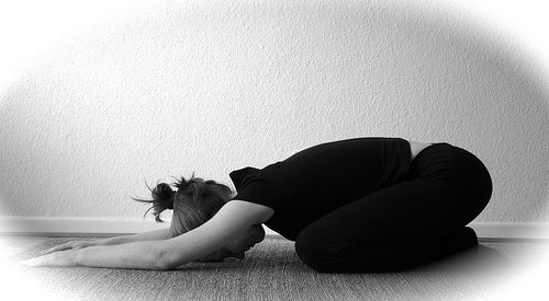black and white photo of a woman doing yoga in child's pose
