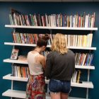 photo of two girls with their backs to the camera looking at a full bookshelf
