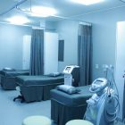 poorly lit hospital room without any people - just cots with dividers and some machines