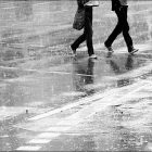 photo of two figures walking in the rain--the photo is in black and white and focused only on their feet and legs as the cross a street