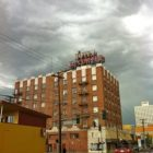 photo of a tall brick building against a gray, stormy sky
