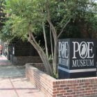"Photo of a sign for the Poe Museum--a raven is illustrated inside of the ""O"""