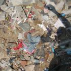 photo of trash in a landfill, the focus of the photo is on the photographer's own silhouette against the trash heap