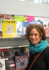 photo of a woman in a turquoise scarf in front of a newsstand of magazines