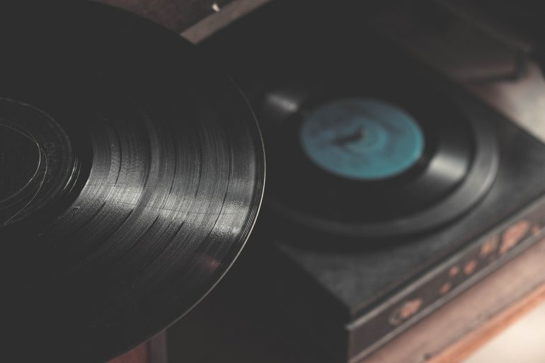 Record player just out of focus beyond a record, in focus with light shining across the grooves of the record
