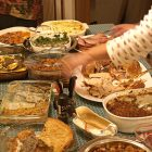 photo of a table of Thanksgiving food, with hands reaching above the food