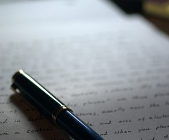 photo of a pen on a page filled the hand-written text