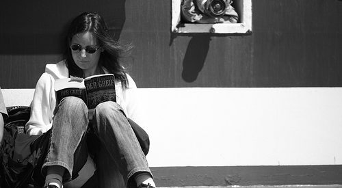 black and white photo of a woman reading against a wall