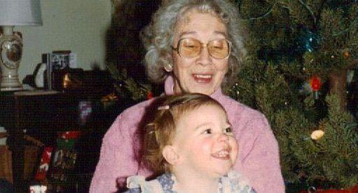 film photo of an older woman in glasses and a pink shirt holding a small child, both in front of a Christmas tree