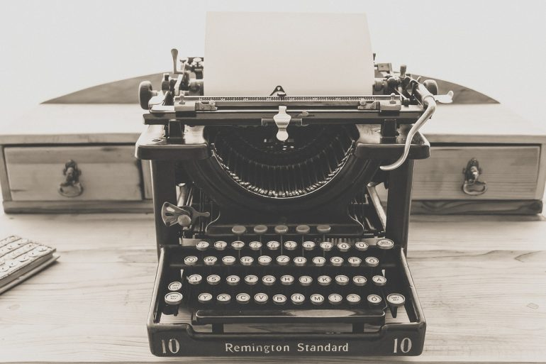 "image of a typewriter sitting on a wooden desk - the typewriter is a ""Remington Standard"" and a blank piece of paper is loaded"