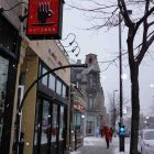 "photo of the front of a cafe on a snowy city street, there is a red sign hanging outside the storefront that reads ""caffe art java"""