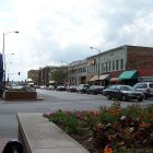 photo of the downtown of Columbia Missouri which feature many cars parked outside a brick storefront street