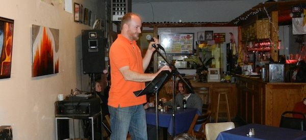 photo of a man in an orange shirt who stands at a mic