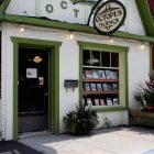 exterior of Octopus Books, which is a cottage style building with green accented doorway and window