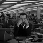 photo of a man sitting a desk in a large office filled with people--he looks exasperated and has his face in his hands