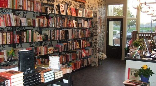 photo of a bookstore interior, with a wall lined with bookshelves