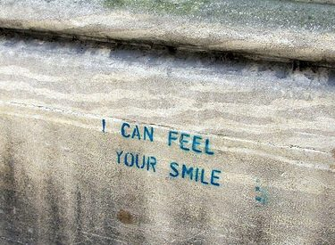 "a wood plank with the words ""I can feel your smile"" written in sharpie"