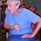 a portrait of Ursula K. Le Guin seated in a chair, in conversation with someone outside of the photograph, she wears jeans and a baby blue tee shirt
