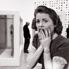black and white photo of a woman dressed in 50s fashion, with a 50s hairstyle - she appears to be in art museum - a man stands behind her, alongside a wall with a large painting - her expression is that of panic or distress, with her hands covering her mouth