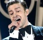 photo of Justin Timberlake in a tuxedo and bowtie performing and singing into a microphone at the Grammies