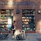 photo of the exterior of St. Mark's Bookshop featuring a sidewalk with a person in motion, walking past a bike rack