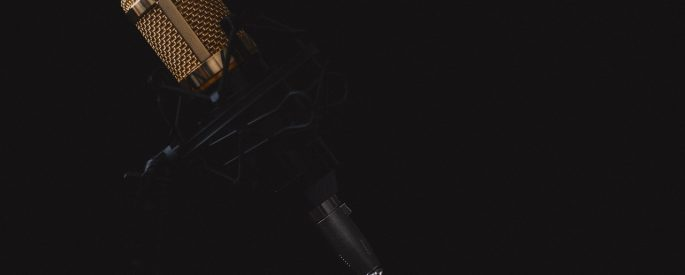 A profile shot of a microphone on a stand in front of a black background.