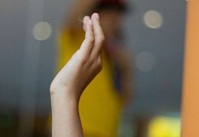 photo of a hand being raised in a question--the focus is on the hand, while the background blurs