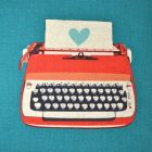 image of a red typewriter on a turquoise background, the paper in the typewriter contains only a turquoise heart