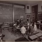 black and white photograph of an old classroom, children sit in a circle with their teacher in front a blackboard with cursive writing across it