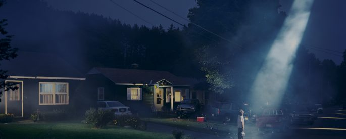 a photograph by the contemporary US photographer Gregory Crewdson of a nighttime suburban scene in which a single figure stands at the end of a driveway with a large beam from some unknown source beaming down on the figure