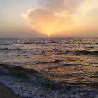 photograph of a beach at sunset with a choppy ocean