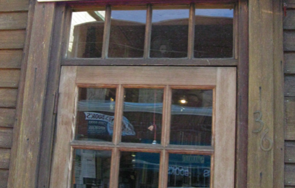 "photograph of the outside of BrattleBoro Books, with a bookstore sign, a subtitle reads: ""Used & Out of Print"""