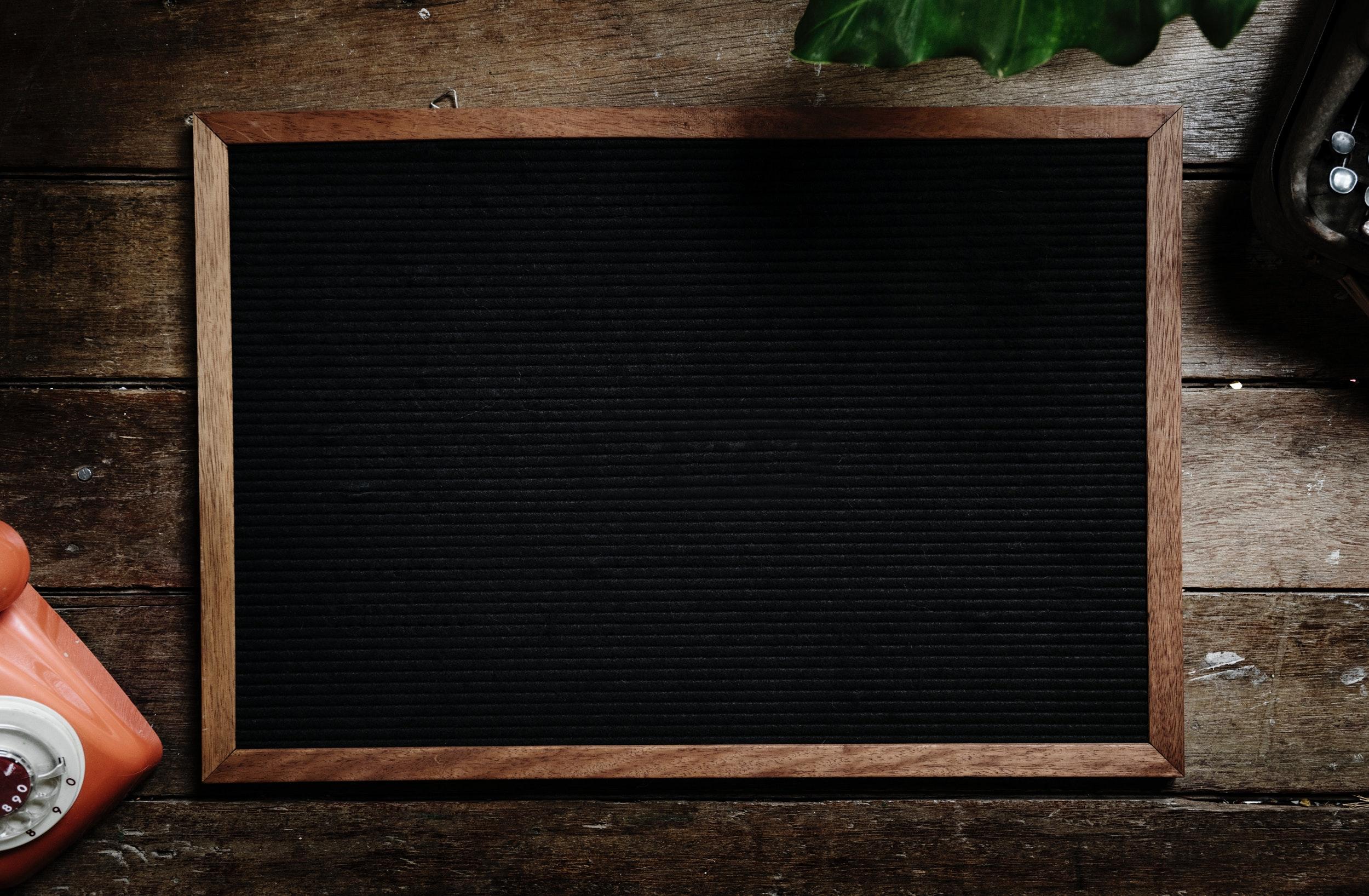 A blank black chalkboard on a wooden table.