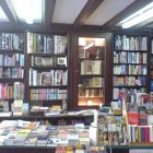 photograph of a bookstore with a multitude of tall floor-to-ceiling shelves and stacks of books
