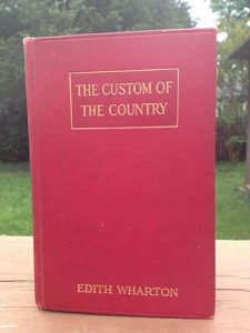 the Custom of the Country by edith wharton has been propped up to stand on top of a picnic bench