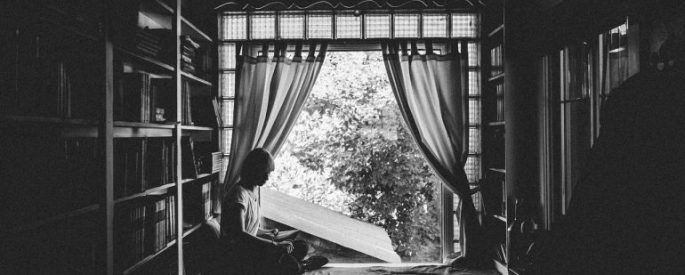 Girl reading by a curtain
