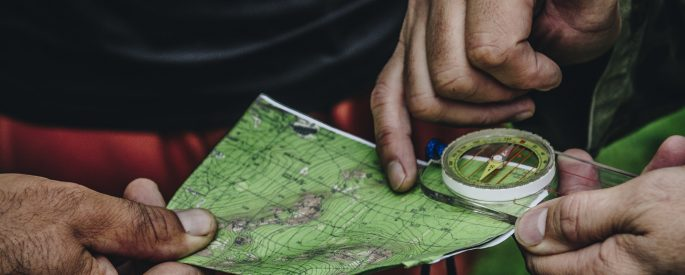 Two men lean over a map and point at it with a compass and look at navigation.