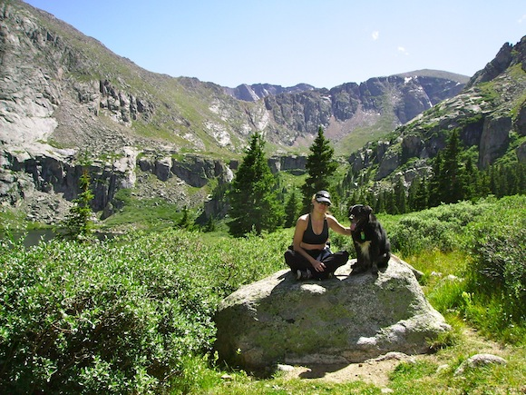 woman and her dog sitting on a rock in the midst of some greenery, trees, and mountains