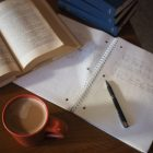 Open book, pen, and cup of coffee